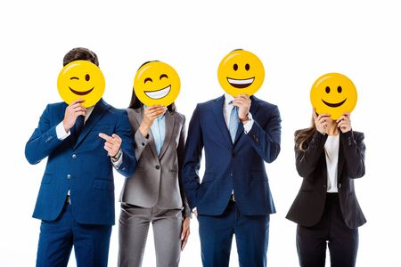 multicultural business people in suits holding emoji in front of faces isolated on white
