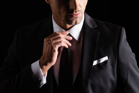 Cropped view of businessman adjusting tie isolated on black