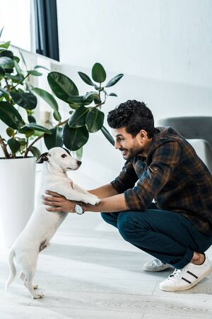 side view of handsome and smiling bi-racial man holding jack russell terrier