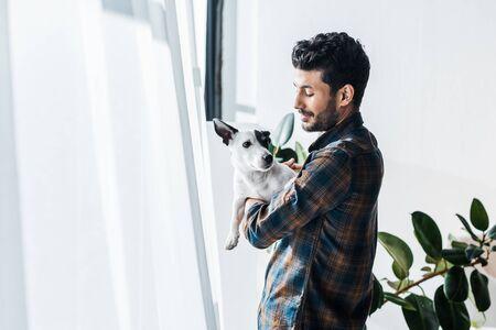 smiling and handsome bi-racial man holding Jack Russell Terrier Standard-Bild
