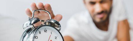 panoramic shot of bi-racial man holding alarm clock in morning