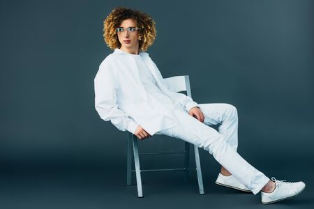 stylish curly teenager in total white outfit and glasses looking away while sitting on chair on green