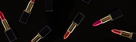 top view of assorted lipsticks in luxury tubes isolated on black, panoramic shot