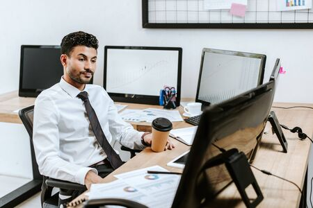 bi-racial trader looking at computer and holding paper cup