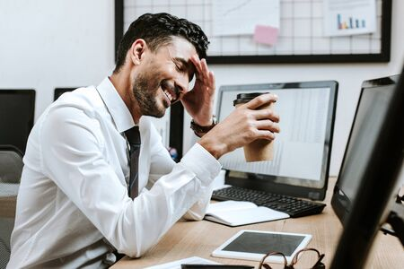smiling bi-racial trader holding paper cup and sitting near computer