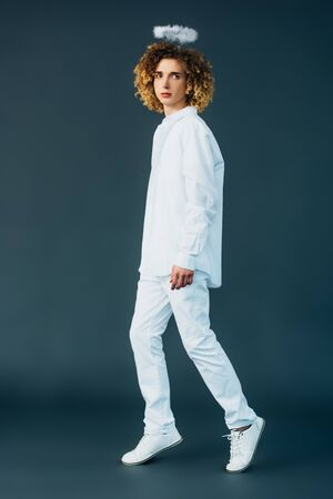 full length view of curly teenager in angel costume with halo above head on green Imagens