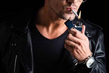 Vue recadrée de l'homme allumant une cigarette avec un briquet isolé sur fond noir