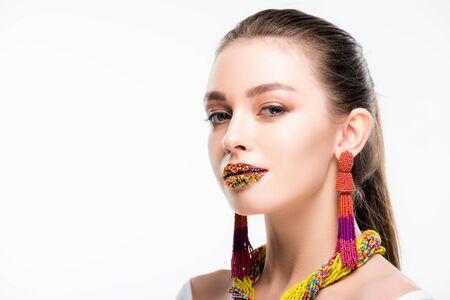 ragazza attraente in accessori di perline, con perline sulle labbra, guardando la telecamera isolata su bianco Archivio Fotografico