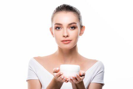 Chica atractiva mirando a la cámara mientras sostiene el recipiente con crema facial aislado en blanco Foto de archivo