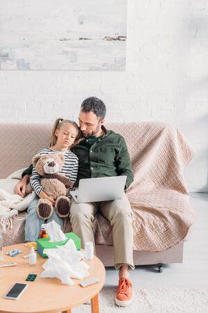 man with diseased, upset daughter sitting on sofa and using laptop