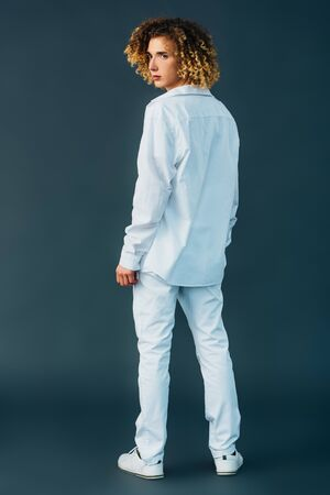 back view of curly teenager in total white outfit isolated on green