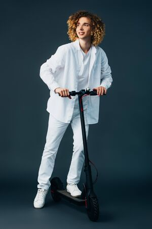 smiling stylish curly teenager in total white outfit riding electric scooter on green