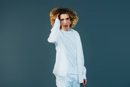curly teenager in total white outfit touching hair isolated on green