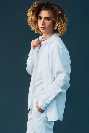 curly teenager in total white outfit with hand in pocket isolated on green