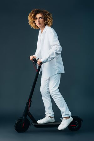stylish curly teenager in total white outfit riding electric scooter on green