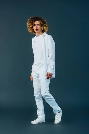 full length view of curly teenager in total white outfit on green