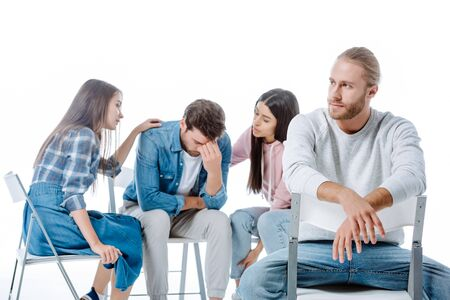 man sitting on chair near multicultural support group helping another man isolated on white Archivio Fotografico