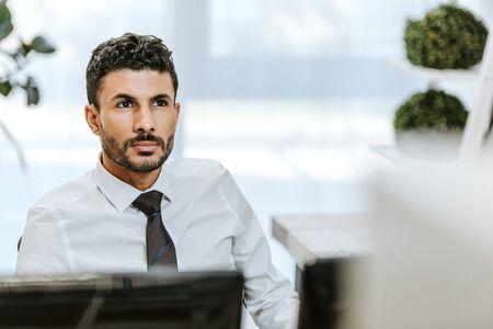 selective focus of handsome bi-racial trader looking away in office Imagens