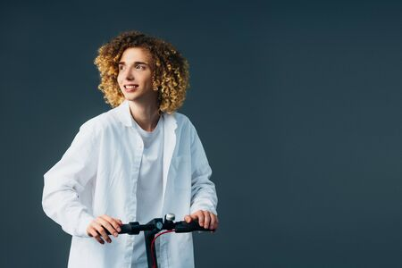 smiling stylish curly teenager in total white outfit riding electric scooter and looking away isolated on green Stok Fotoğraf