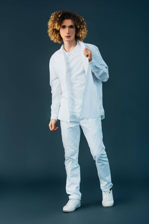 full length view of curly teenager in total white outfit posing isolated on green