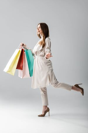 full length view of happy girl in stylish cape holding shopping bags on grey background