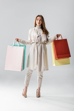 full length view of stylish girl looking away while holding shopping bags on grey background 스톡 콘텐츠