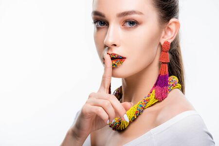 attractive girl in beaded accessories, with beads on lips, showing hush sign and looking at camera isolated on white