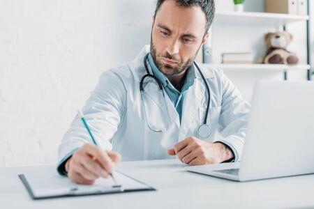 selective focus of attentive doctor writing prescription on clipboard Banco de Imagens