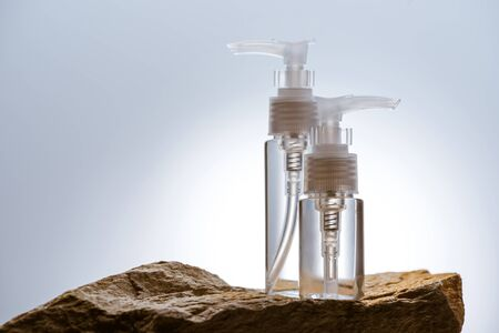 dispenser cosmetic bottles on stone on white background with back light
