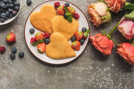 top view of heart shaped pancakes with berries on grey concrete surface near roses