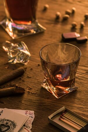 KYIV, UKRAINE - NOVEMBER 7, 2019: Glass of brandy with cigars, matches and playing cards on table