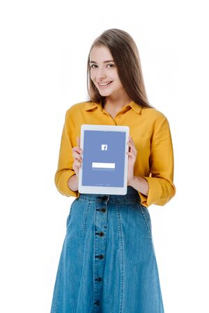 KYIV, UKRAINE - AUGUST 12, 2019: smiling girl in denim skirt holding digital tablet with Facebook app isolated on white Editorial