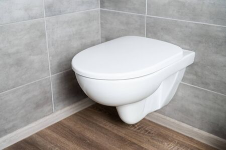 Clean white toilet bowl in restroom with grey tile