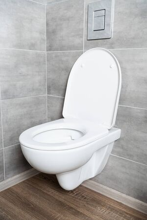 White toilet bowl with open seat in restroom with grey tile