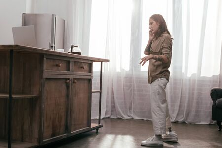 Side view of young woman with prosthetic leg talking on smartphone at home 版權商用圖片