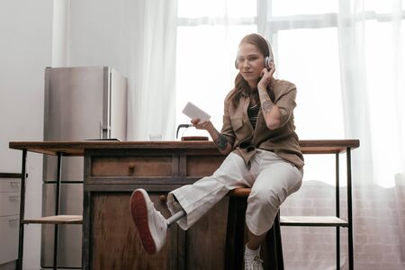 Young woman with prosthetic leg using headphones and holding smartphone be kitchen table 版權商用圖片