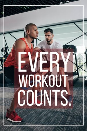 attentive trainer supporting african american sportsman near illustration with every workout counts inscription