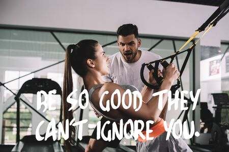 excited trainer shouting while motivating sportswoman pulling up on suspension trainer near illustration with be so good they cant ignore you inscription