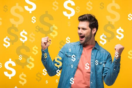 happy handsome man showing yes gesture isolated on yellow with dollars icons