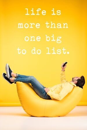 man relaxing on bean bag chair and using smartphone on yellow background with life is more than one big to do list illustration