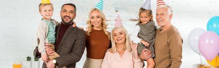 panoramic shot of happy family posing at camera in party caps Standard-Bild