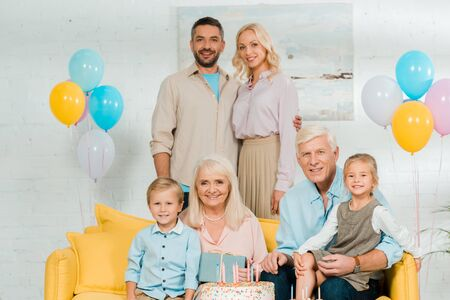 happy family looking at camera near birthday cake and colorful festive balloons