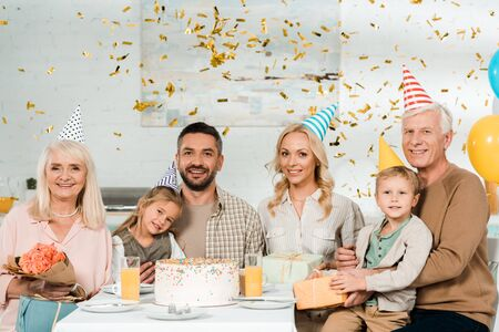 cheerful family sitting at kitchen table near birthday cake under falling confetti and smiling at camera