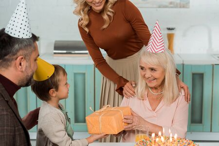 cropped view of woman touching shoulders of happy granny taking gift box from grandson