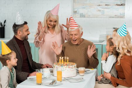 excited senior man looking at birthday cake with burning candles while sitting at served table near family Standard-Bild