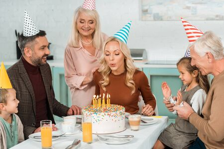 happy woman blowing out burning candles on birthday cake near family sitting at kitchen table