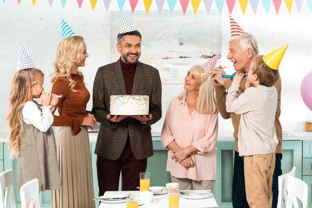 happy man holding birthday cake near cheerful family in party caps