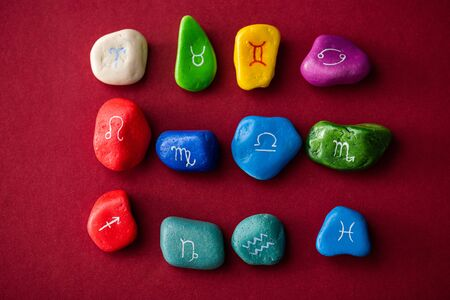 Top view of colorful stones with zodiac signs on red surface