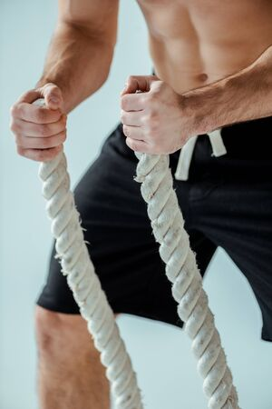 cropped view of sexy muscular bodybuilder with bare torso exercising with battle rope isolated on grey Banque d'images