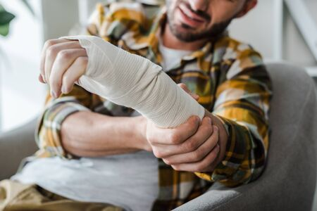 selective focus of injured arm of bearded man in bandage